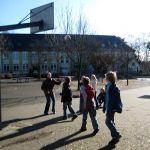 Die Schachgruppe spielt während ihrer Pause unter Aufsicht Basketball und genießt dabei die frische Luft und die warmen Sonnenstrahlen.