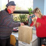 Im Team Naturschutz hilft Herr Reuter gerade einer Schülerin dabei, die Schrauben an ihrem Fledermauskasten festzuziehen.